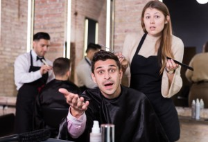 Unpleasantly surprised man with regretting woman hairdresser in