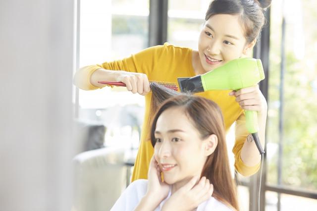 お客様の髪をブローする美容師